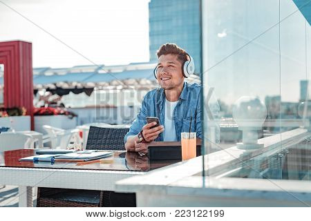 What if. Waist up shot of a handsome young man beaming while listening to music and dreaming after working on his home assignment.