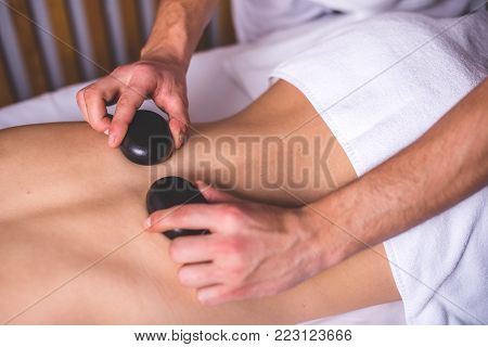 Male hands hold hot stones on the female back. The lower part of the body is covered with a white towel. Stone therapy.
