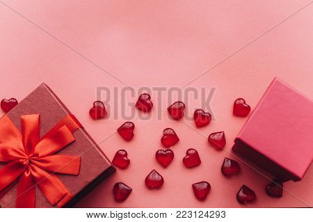 Red beautiful box with ribbon and bow and next to another red box with gifts on red background. Nearby are symbols in the form of a heart. Celebration. Event.