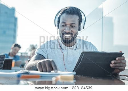 Education is the key to success. Low angle shot of a cheerful college guy smiling while enjoying the music playing in his headphones and working on a home assignment.