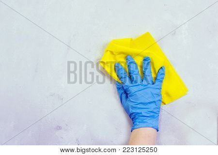 Woman in protective gloves cleaning kitchen table with rag.  Day of cleanliness and cleaning.