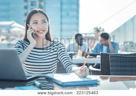 Work is calling. Positive minded young woman smiling while sitting at a table and taking some notes during a pleasant phone conversation.