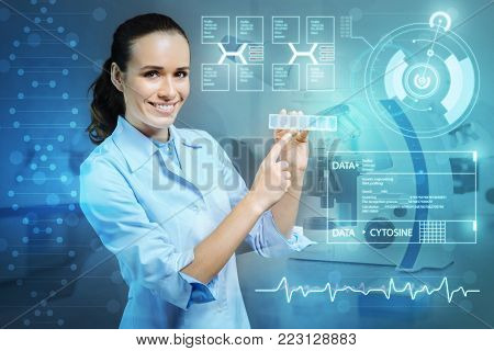 Cheerful doctor. Kind clever experienced doctor looking happy while showing a necessary pillbox in her hands and smiling
