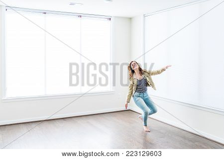 One young happy smiling woman jumping up in empty modern new room with hardwood floors and large sunny windows in apartment