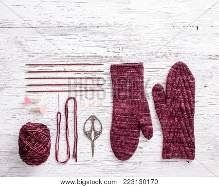 Red mitten with knitting needles, yarn and knitting accessories on white wooden background. Copy space. Free space for text. Top view. Knolling knitting