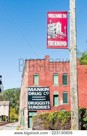 Thurmond, USA - October 19, 2017: Railroad rail, abandoned closed brick buildings with welcome sign in West Virginia ghost town village