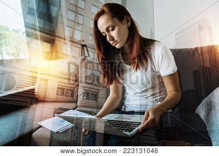 Unsatisfying news. Young serious woman feeling disappointed while sitting on a sofa with a laptop on her knees and looking at the screen of it