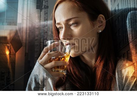 Drinking alcohol. Young exhausted woman looking into the distance and feeling miserable while drinking alcohol