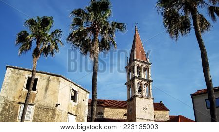 View from below to the tower of church of Lady of Blessing in town Milna in Croatia at sunny day,and three palm trees