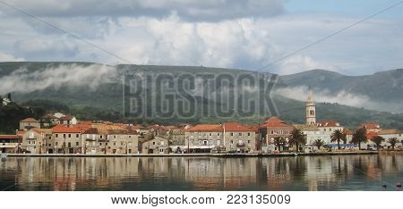 Beautifull Panoramic view on old town Jelsa on cloudy day and hills with fog,reflection