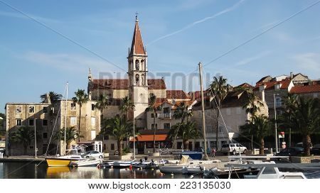 Ancient church of Lady of Blessing next to marina in town Milne and a lot of green palm trees