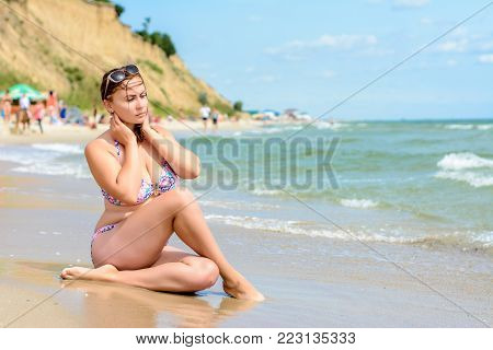 A Young Brunette Sits In A Swimsuit On The Odessa Beach In Ukraine. A Young Brunette With Neat Shape
