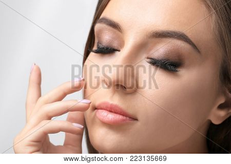 Beautiful young woman with eyelash extensions on light background, closeup