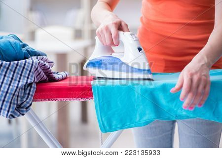 Woman wife doing ironing at home