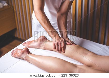 A male massage therapist massages the female legs in the massage parlor. Hands of the masseur make a foot massage lying on the couch. Legs lie on a white couch against the background of wooden walls.