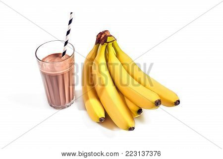 Chocolate banana smoothie in a glass with straws on white background. Glass of chocolate milk with ripe yellow bananas. Still life. Copy space