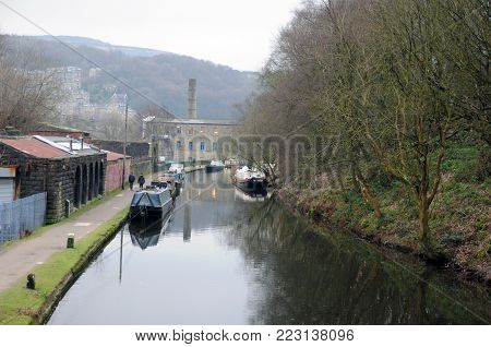 view of the rochdale canal outside hebden bridge with the town and mill buildings in the distance reflected in the water on a winters day