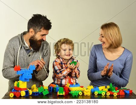 Family With Excited Faces Build Out Of Colored Construction Blocks