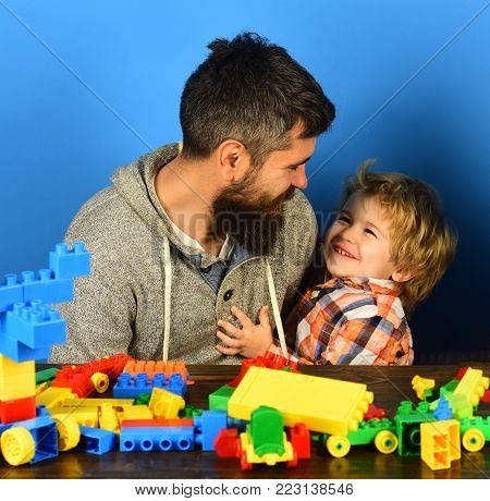Family with cheerful faces build toy cars out of colored construction blocks. Father and kid spend time in playroom. Childhood and playing concept. Man with beard and boy play on blue background.