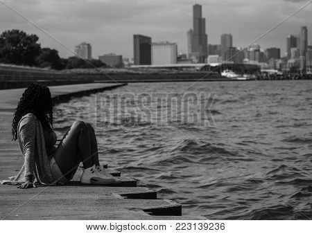 Girl sitting by the water at the lake front enjoying the view of the skyline
