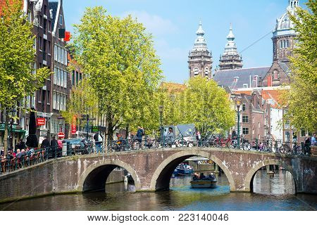 Amsterdam, Netherlands - April 20, 2017: Bridge, canal and St. Nicolas Church in Amsterdam. Amsterdam is the capital and most populous city of the Netherlands