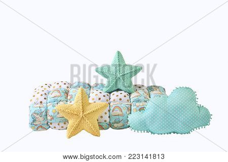 Yellow and blue-green knitted five-pointed star shaped pillows, patchwork comforter and cloud shaped blue pillow on white background