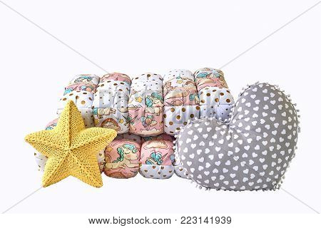 Yellow knitted five-pointed star shaped pillow, patchwork comforter and heart shaped pillow on white background