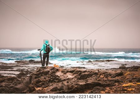 Photograph with a dog looking for motive. Waves hitting volcanic rocky coastline. Sahara dust in the sky. Santo Antao Island, Cape Verde.