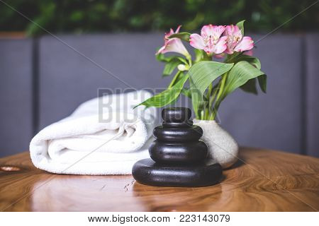 Beautiful view of the towel and massage stones on the table. White-pink daffodils stand in a white vase. Pyramids of stones for massage lie on the wooden table. White towels lie in the background.