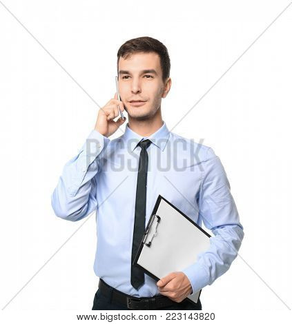 Handsome car salesman talking on mobile phone against white background