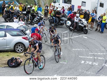 Col du Glandon, France - July 24, 2015: Four cyclists (Frank and Clement of IAM, Barguil of Giant-Alpecin and Thibaut Pinot of FDJ),climbing the road to Col du Glandon in Alps, during the stage 19 of Le Tour de France 2015.