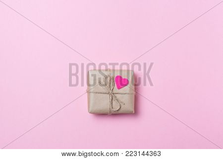 Gift In Craft Paper With Pink Heart On Pink Background. Love Concept. Saint Valentine's Day Concept.