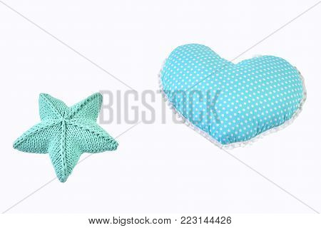 Blue-green knitted five-pointed star shaped pillow and dotted blue heart shaped pillow on white background