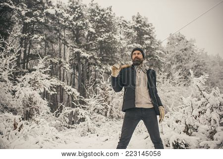 skincare and beard care in winter, beard warm in winter. Camping, traveling and winter rest. Man lumberjack with ax. Temperature, freezing, cold snap, snowfall. Bearded man with axe in snowy forest.