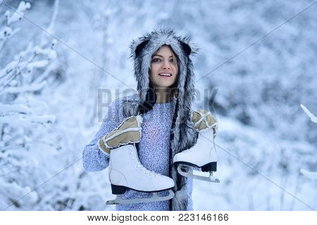 Sport, activity, health. Happy woman smile with figure skates at trees in snow. Vacation, holidays, hobby, lifestyle. Girl with skating shoes in winter clothes in snowy forest. Ice skating concept.