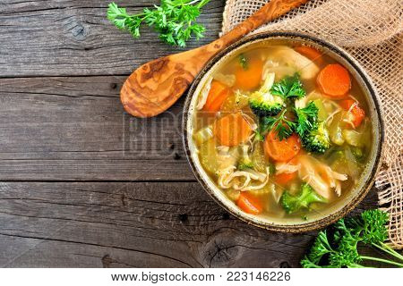 Homemade chicken vegetable soup, above view with copy space on a rustic wooden background