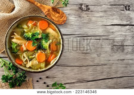 Homemade chicken vegetable soup, above view side border with copy space on a rustic wooden background