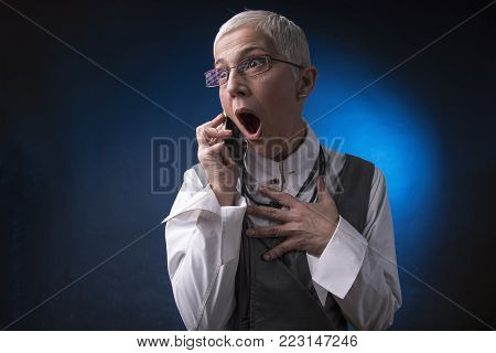 Shocked and appalled senior business woman overreacting to some bad news she receives over her cell phone, blue background