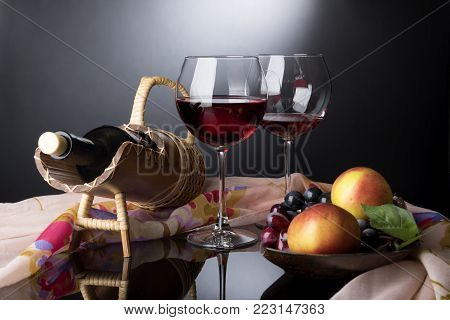 Two red wine glasses, bottle in straw prop and wooden plate with vines and apples situated on black mirror tablecovered by rosy cloth on dark background