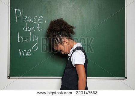 "African-American girl near chalkboard with text ""Please don't bully me"" poster"