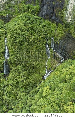 Multiple waterfalls running down Napali Coast mountains. Taken from a helicopter on Kauai Hawaii.