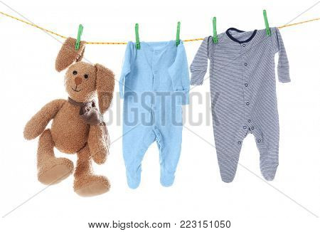 Children's clothes and toy on laundry line against white background