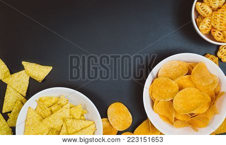 Party snacks - potato chips and snacks in bowl on black slate table. Photograph taken from above, top view with copy space around products.