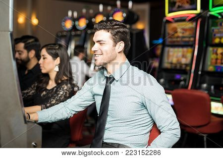 Handsome young man having some fun playing in a slot machine in a casino