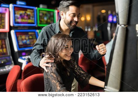 Portrait of an excited young Latin couple winning some money in a slot machine in a casino
