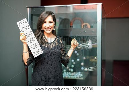 Excited young woman showing her ticket after winning a bingo game in a casino