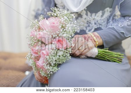 Bride hand with henna and a bouquet of flower