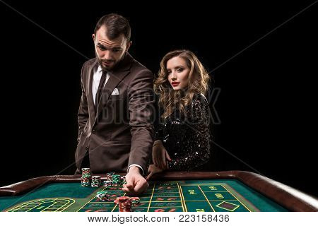 A man in a suit with a woman in a beautiful black dress playing roulette at the casino. Gambling. Casino. Roulette. Poker.