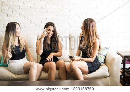 Cute female friends and roomies getting ready to go out at night and making plans on the phone