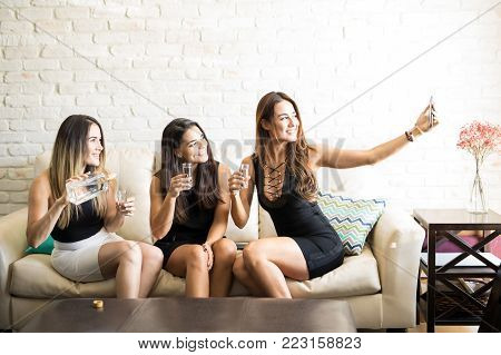 Gorgeous female friends all dressed up and drinking tequile while taking a selfie